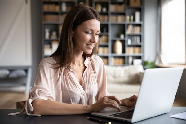 Happy young woman browsing internet on laptop